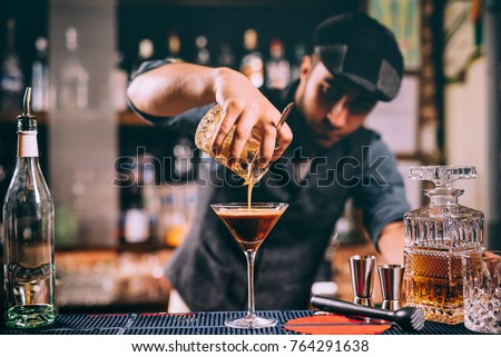 Vintage portrait of bartender creating cocktails at bar. Close up of alcoholic beverage preparation #764291638