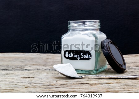 Jar and spoonful of baking soda on wooden table #764319937