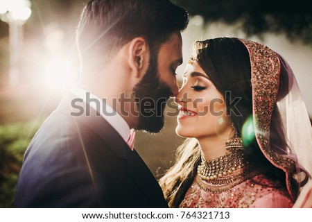 Handsome bearded Indian groom kisses bride in pink dress tender standing outisde #764321713