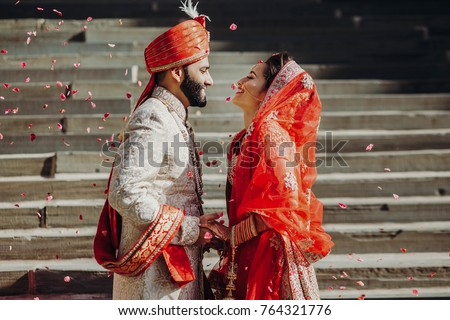 Indian groom dressed in white Sherwani and red hat with stunning bride in red lehenga stand and hold each hands walking outside #764321776