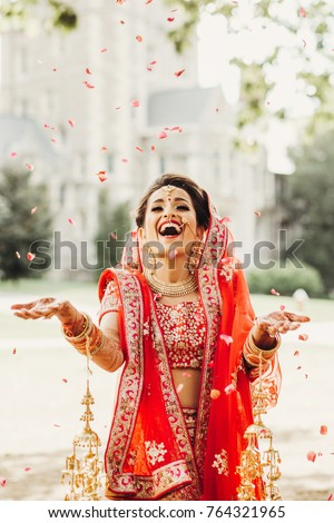 Stunning Indian bride dressed in Hindu traditional wedding clothes lehenga embroidered with gold and a veil smiles tender posing outside with golden accessories under the rain of petals #764321965