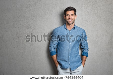 Portrait of a handsome man smiling against grey background with copy space. Smiling latin guy with hands in pocket in blue shirt standing and leaning on wall. Successful hispanic man looking at camera #764366404