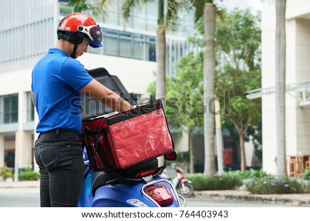 Delivery man taking food out of bag on his scooter #764403943
