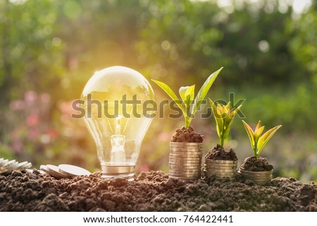 Energy saving light bulb and tree growing on stacks of coins on nature background. Saving, accounting and financial concept. #764422441