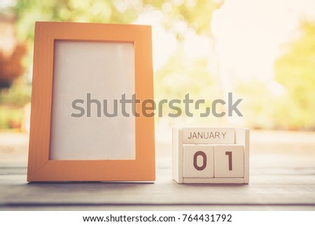 January 1st. white wooden calendar with picture frame on wooden table background.