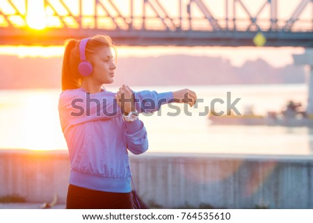 Young beautiful girl with headphones on her head stretching and listening music before jogging with river and bridge on background at sunset #764535610