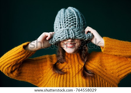 Beautiful young happy smiling girl hiding her eyes under trendy grey big loop knitted beanie hat. Model wearing winter sweater. Close up