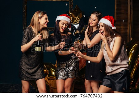Happy smiling girls In stylish glamorous outfit with champagne glasses at Christmas party. #764707432