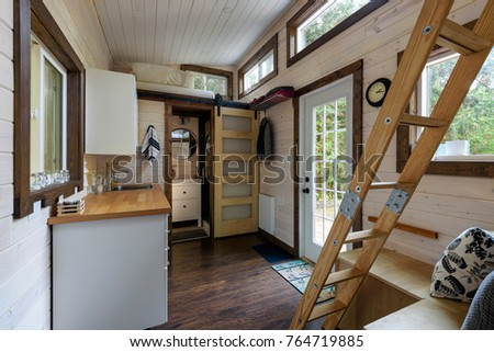 Interior design of a dining room and kitchen in a tiny rustic log cabin. Royalty-Free Stock Photo #764719885