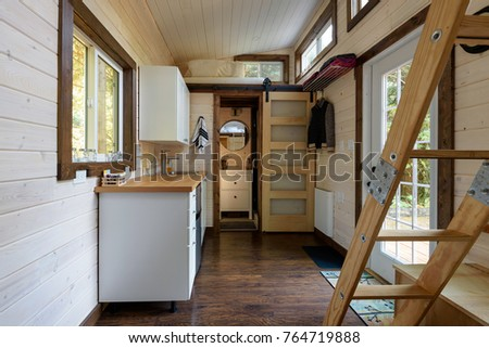 Interior design of a dining room and kitchen in a tiny rustic log cabin. Royalty-Free Stock Photo #764719888