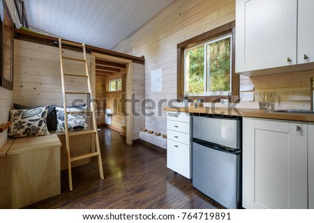 Interior design of a dining room and kitchen in a tiny rustic log cabin. #764719891