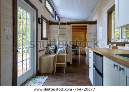 Interior design of a dining room and kitchen in a tiny rustic log cabin. Royalty-Free Stock Photo #764720677