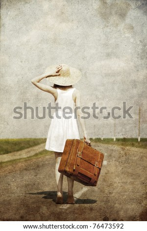 Lonely girl with suitcase at country road.. Photo in old image style. #76473592