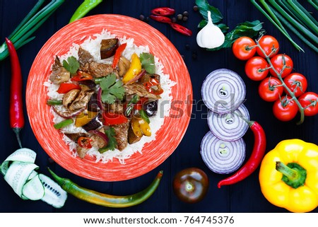 Tasty spicy stir-fry pork meat with rice and roasted vegetables, flat lay on dark background with ingredients. Delicious food, Pan-Asian, oriental cuisine #764745376