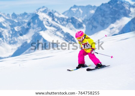 Child skiing in mountains. Active toddler kid with safety helmet, goggles and poles. Ski race for young children. Winter sport for family. Kids ski lesson in alpine school. Little skier racing in snow #764758255