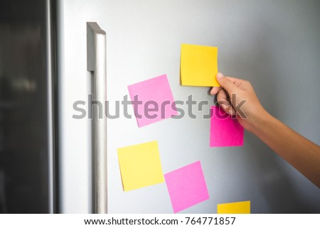 hand holding blank sticky paper note on refrigerator door #764771857