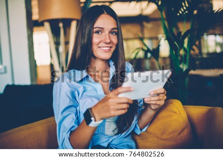 Attractive young woman resting in cafe interior booking room in hotel online via portable pc, cute hipster girl looking at camera checking banking account on tablet for making money transaction #764802526