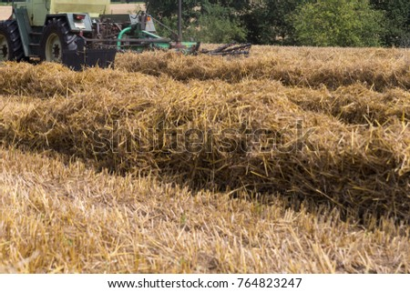 tractor haying straw on summer corn field in south germany countryside #764823247