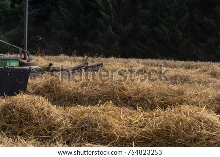 tractor haying straw on summer corn field in south germany countryside #764823253