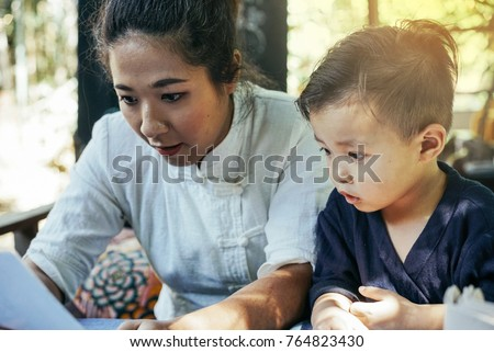 happy asian mother and son using smartphone #764823430