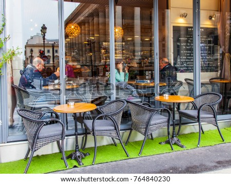 PARIS, FRANCE, on October 27, 2017. The attractive cafe with little tables on the street expects visitors in the morning. The city is reflected in a big window #764840230