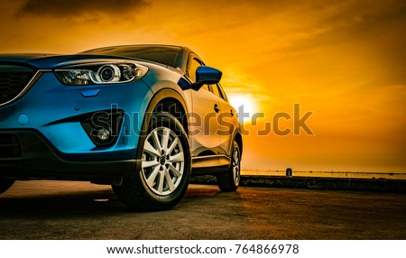 Blue compact SUV car with sport and modern design parked on concrete road by the sea at sunset. Environmentally friendly technology. Business success concept. #764866978