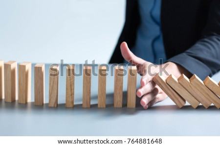 Risk management Businesswoman stop domino effect. leadership has solution for problem.  #764881648