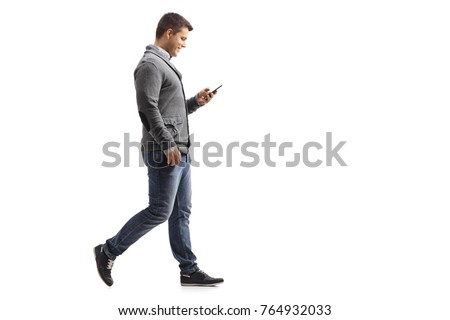 Full length profile shot of a young man walking and using a phone isolated on white background #764932033