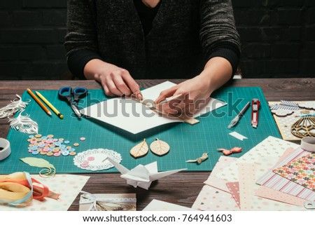 cropped image of designer cutting paper for scrapbooking greeting postcards Royalty-Free Stock Photo #764941603