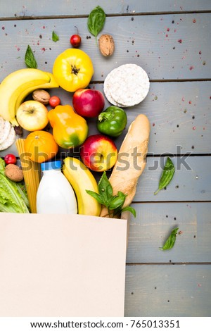Grocery shopping concept. Different food in paper bag on wooden background.  Flat lay #765013351