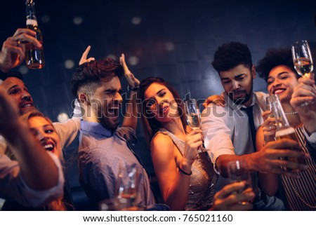 Group of friends celebrating at a nightclub Royalty-Free Stock Photo #765021160