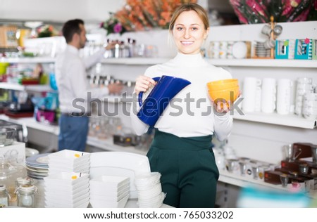 Smiling girl showing off buying a pottery in a store #765033202