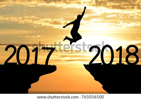 Silhouette  man jumping on top mountain from 2017 to 2018 new year,sunset background. copy space for text. Successful concept. #765056500