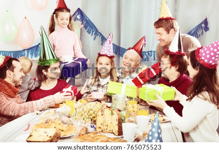 Large family handing gifts to birthday girl during dinner #765075523
