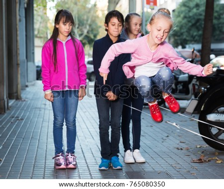 Positive children play on city sidewalk in autumn city #765080350