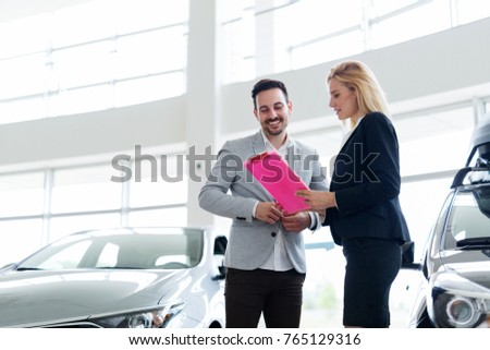 Professional salesperson selling cars at dealership to buyer #765129316