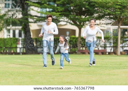 happy Asian family running together on garden - Parents and daughters happiness running in park #765367798