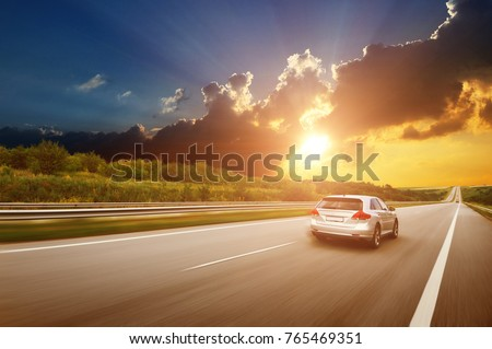 A silver crossover car driving fast on the countryside asphalt road against night sky with clouds and a beautiful sunset #765469351