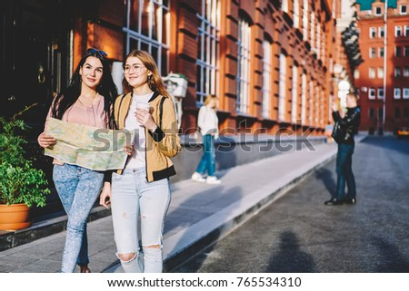 Positive teen girl traveling together having city tour in European downtown with ancient architecture, smiling female best friends strolling with map passing urban settings copy space for advertising #765534310