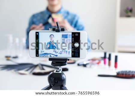 Happy smiling elegant woman or beauty blogger with brush on recording video while review product make up tutorial for theme about video blogging on camera screen. #765596596