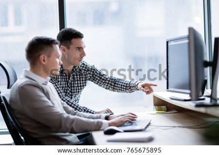 Picture of businesspeople working on computer together Royalty-Free Stock Photo #765675895