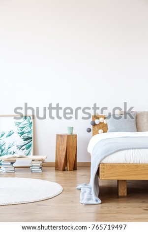 Wooden shelf standing in front of a green painting, supported by two piles of books next to a modern coffee stand #765719497