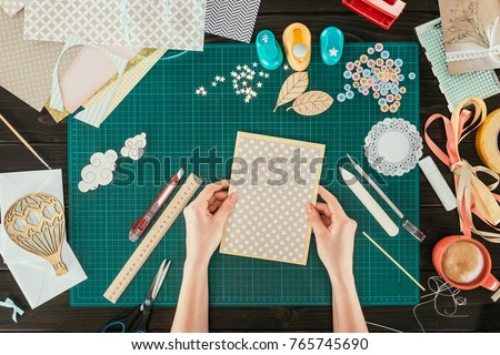 cropped image of designer holding template for scrapbooking postcard Royalty-Free Stock Photo #765745690