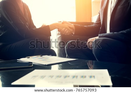 Buseness meeting and successful concept - close up of two smiling businessman and businesswoman shaking hands after they have good deal in executive room at office, startup business project plan #765757093