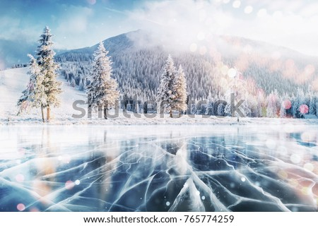 Cracks on the surface of the blue ice. Frozen lake in winter mountains. It is snowing. The hills of pines. Carpathian Ukraine Europe. Royalty-Free Stock Photo #765774259