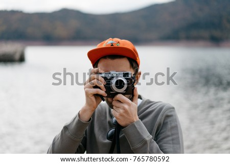 space for text, logo attractive hipster guy holding photo camera. handsome traveler shooting outdoor. mock up, young man taking pictures in the nature