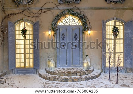 House decorated for Christmas outside. Vintage courtyard interior with stairs, porch, door and lights in windows. Winter christmas background. #765804235