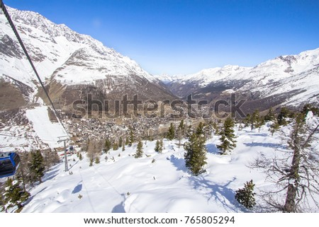 Swiss village surrounded by a snow-covered mountain range in Saas Fee #765805294