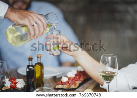 Hand of cropped unrecognisable man ouring drink to woman at lunch. #765870748