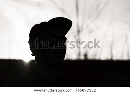 silhouette of main in ball cap against winter sunset #765899152